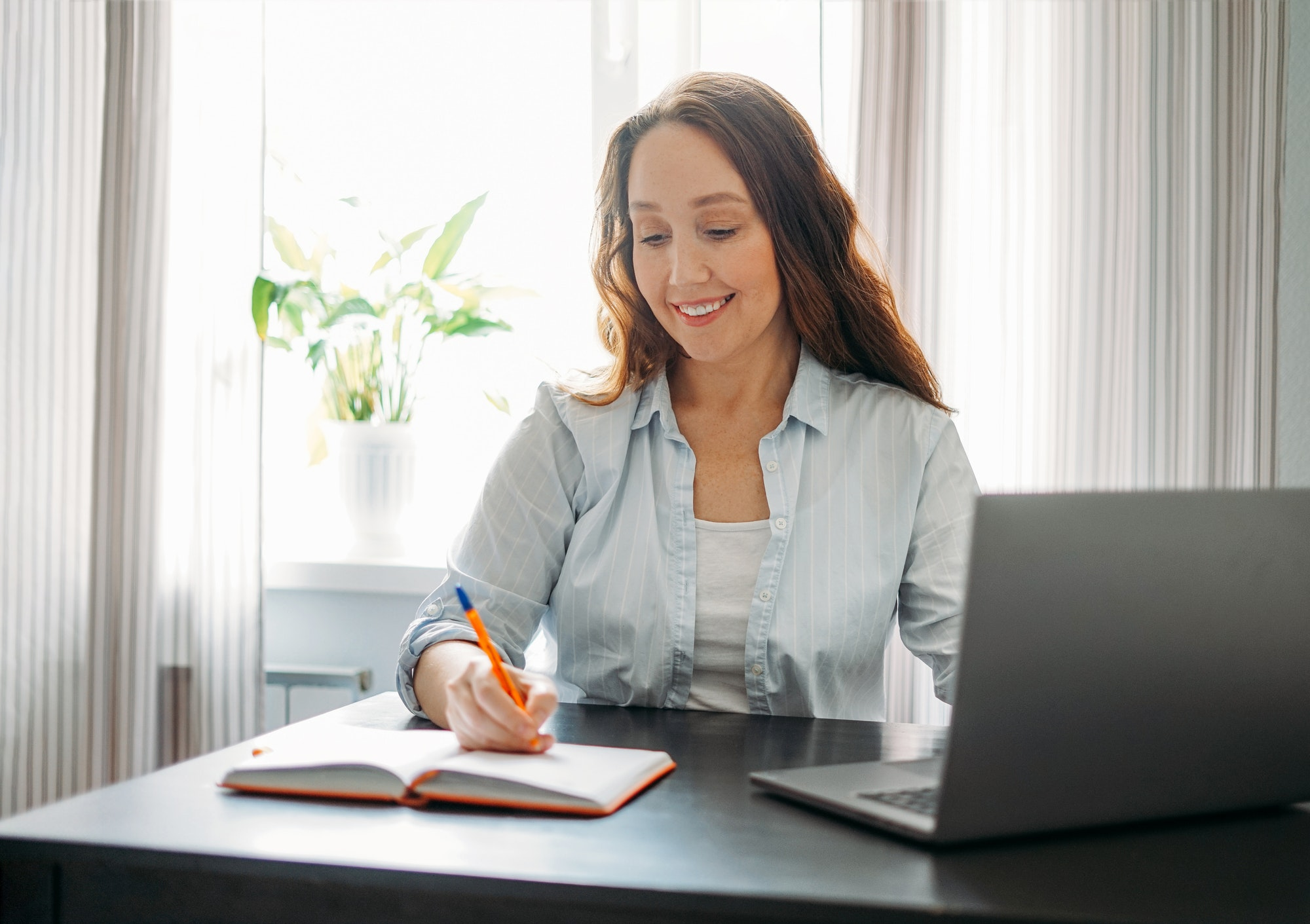 Adult smiling brunette woman doing notes in daily book with opened laptop